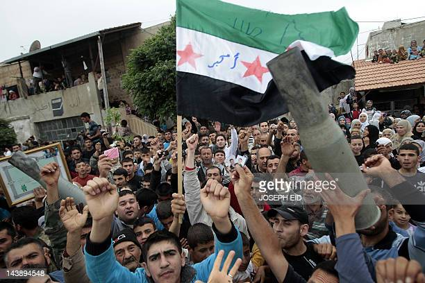 Syrian antiregime protesters wave the preBaath Syrian flag while holding the remains of fired ammunition as they greet UN observers in the village of...