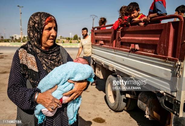 Syrian Arab and Kurdish civilians arrive to Tall Tamr town in the Syrian northwestern Hasakeh province after fleeing Turkish bombardment on the...