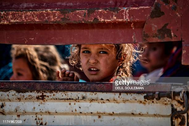TOPSHOT Syrian Arab and Kurdish civilians arrive to Tall Tamr town in the Syrian northwestern Hasakeh province after fleeing Turkish bombardment on...