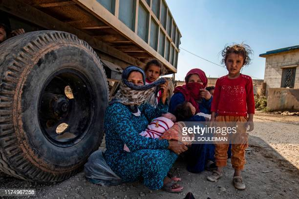 Syrian Arab and Kurdish civilians arrive to Tall Tamr town, in the Syrian northwestern Hasakeh province, after fleeing Turkish bombardment on the...