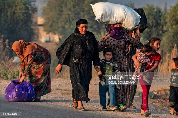 Syrian Arab and Kurdish civilians flee amid Turkish bombardment on Syria's northeastern town of Ras alAin in the Hasakeh province along the Turkish...