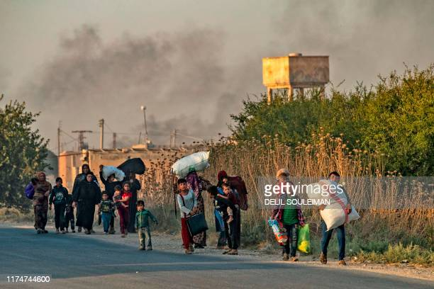 TOPSHOT Syrian Arab and Kurdish civilians flee with their belongings amid Turkish bombardment on Syria's northeastern town of Ras alAin in the...