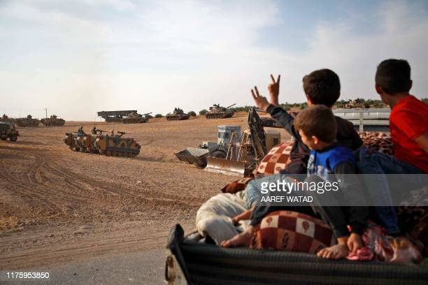 Syrian Arab civilians flash the victory sign as Turkish armoured personnel carriers and US-made M60 taks gather in the village of Qirata on the...