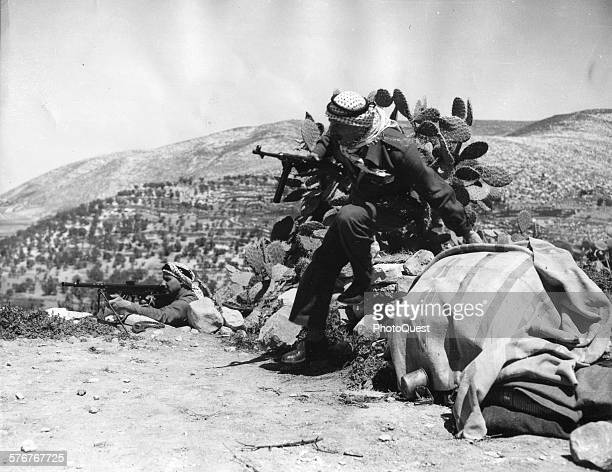 A Syrian Arab leaps over a wall while he received covering fire from an outdated French light machine gun near Jerusalem Palestine April 17 1948