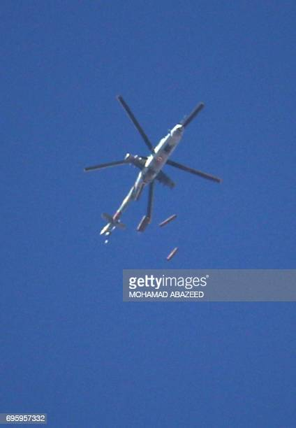 A Syrian army helicopter drops barrel bombs on a rebelheld area in the southern city of Daraa on June 14 2017 / AFP PHOTO / Mohamad ABAZEED