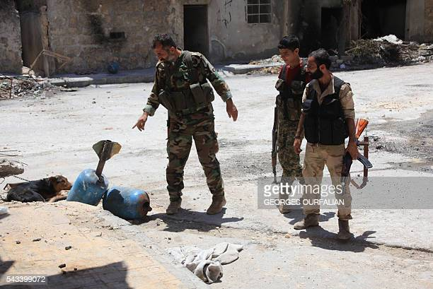 Syrian army soldiers check unexploded homemade rockets during a patrol in governmentcontrolled Aleppo's alKhalidiya area where the army progressed...