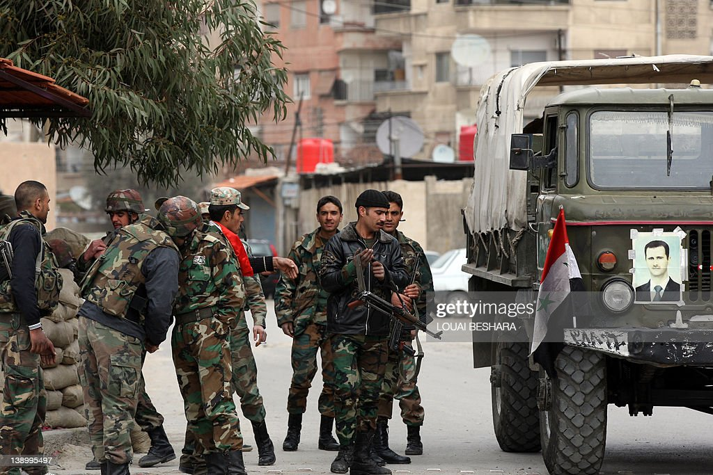 Syrian army soldiers stand at a checkpoi : News Photo
