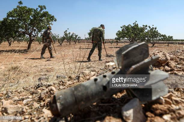 Syrian army soldiers use detectors to find and clear landmines in a field at a pistachio orchard in the village of Maan, north of Hama in...
