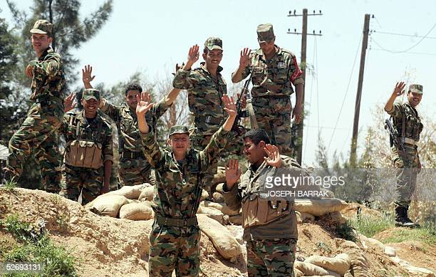 Syrian army special forces wave as they prepare to leave their position in the Lebanese town of Baalbek 25 April 2005 Syrian troops were packing up...