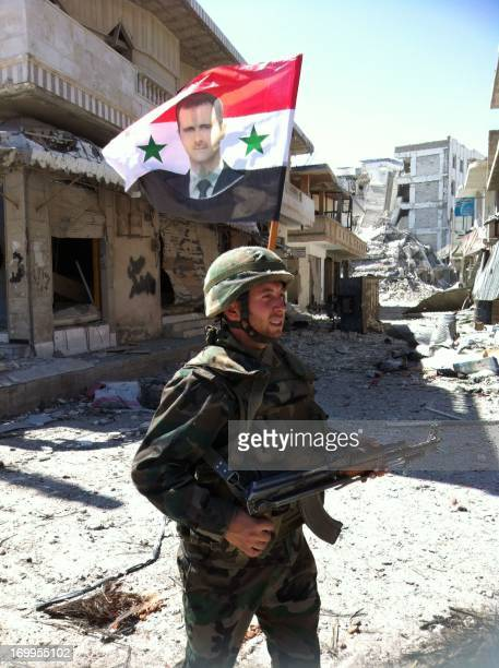 A Syrian army's soldier walks in a street left in ruins with a national flag featuring Syria's President Bachar alAssad on June 5 2013 in the city of...