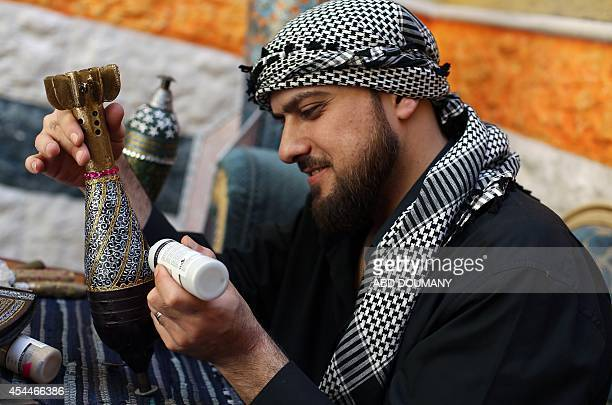 Syrian artist Akram Abu AlFawz paints on a mortar shell on May 30 2014 in Douma a rebelheld town near Damascus The artist who uses a traditional...