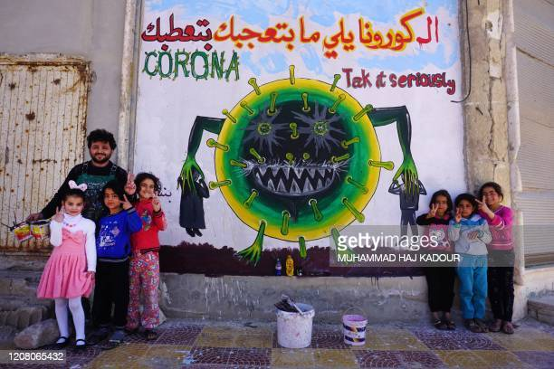Syrian artist Aziz al-Asmar and children flash the victory gesture as they pose next to a freshly-drawn graffiti of a cartoon depiction of the...