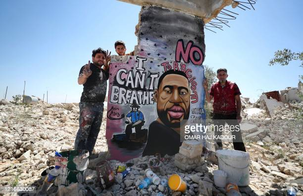 TOPSHOT Syrian artists Aziz Asmar and Anis Hamdoun finish a mural depicting George Floyd an unarmed AfricanAmerican man who died while while being...