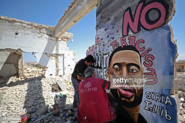 Syrian artists Aziz Asmar and Anis Hamdoun paint a mural depicting George Floyd an unarmed AfricanAmerican man who died while while being arrested...
