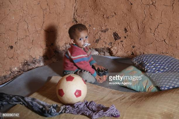 Syrian baby sits on the floor during Muslim's holy month of Ramadan in Idlib Syria on June 23 2017 Ahead of Eid al Fitr Syrian people who fled from...
