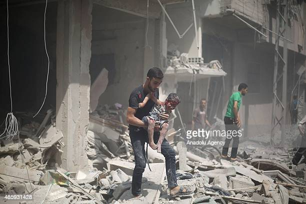 Syrian baby wounded by Assad regime forces' airstrike staged to residential areas is being carried by a man to hospitalize in Douma District of East...
