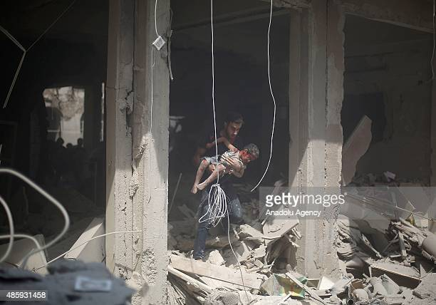 Syrian baby, wounded by Assad regime forces' air-strike staged to residential areas, is being carried by a man to hospitalize in Douma District of...