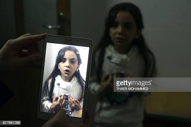 Syrian Bana alAbed is filmed by her mother as they prepare to post on Twitter in English about life in the besieged eastern districts of Syria's...