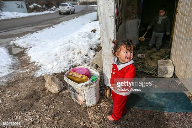 Syrian barefoot child stands outside makeshift tent surrounded by snow in Turkey's Van province on December 22 2016 As the weather cools down Syrian...