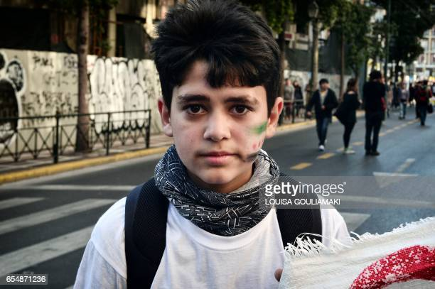 TOPSHOT A syrian boy bearing a painted Syrian flag used by the Syrian National Coalition and nicknamed the 'Independence flag' on his cheek takes...
