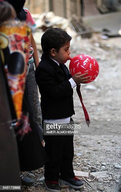 A Syrian boy blows a balloon during an activity organised by a charity group in Jobar a rebelheld district on the eastern outskirts of the capital...