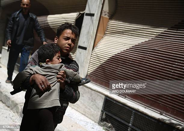 A Syrian boy carries a child while he runs for cover in the rebelheld area of Douma east of the capital Damascus as several air strikes pounded the...
