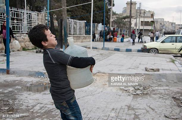 A Syrian boy carries a container filled with water on February 23 2016 in the rebelheld side of the northern city of Aleppo A landmark ceasefire has...