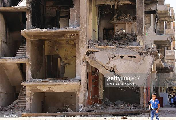 Syrian boy carries a toy gun past a destroyed building in the northeastern Syrian city of Qamishli on September 13 2016 as a truce brokered by Russia...