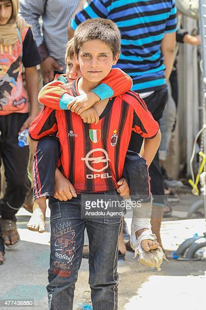 Syrian boy carries a wounded kid on his back as they return to the Syrian town of Tal Abyad from Turkey near Akcakale border crossing in Sanliurfa...