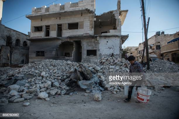 Syrian boy carries buckets as he passes through a wrecked building in AlBab district of Aleppo Syria on March 27 2017 Life returns back to normal...