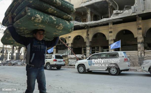 Syrian boy carries mattresses over his head while walking past vehicles of the UN and the International Committee of the Red Cross delivering...