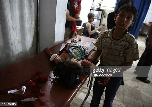 A Syrian boy comforts a wounded girl as they wait for treatment at the Unified Medical Office for Douma a makeshift medical centre in the rebelheld...