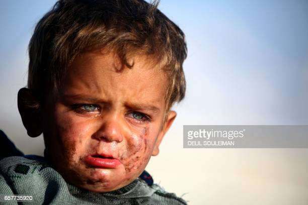 Syrian boy cries as he is being held at a temporary refugee camp in the village of Ain Issa housing people who fled Islamic State group's Syrian...