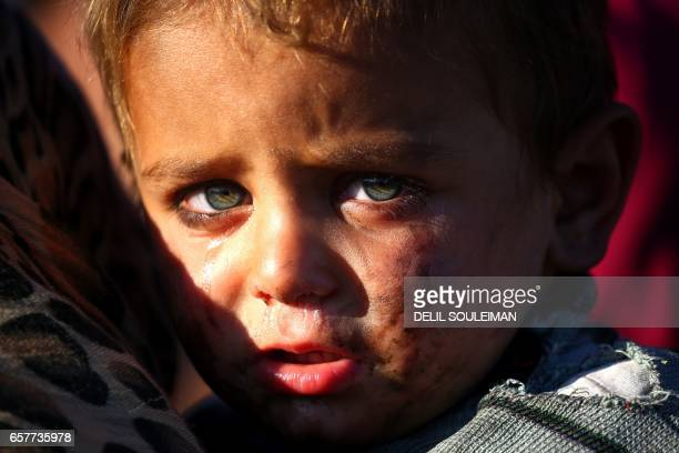 A Syrian boy cries as he is being held at a temporary refugee camp in the village of Ain Issa housing people who fled Islamic State group's Syrian...