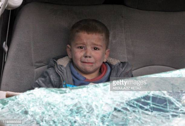 Syrian boy cries as he is evacuated after a regime air strike on Ariha town in Syria's last major opposition bastion of Idlib on January 15, 2020. -...