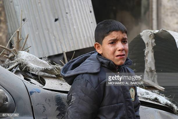 Syrian boy cries as he stands next to a building hit by an air strike on the village of Maaret alNuman in the country's northern province of Idlib on...