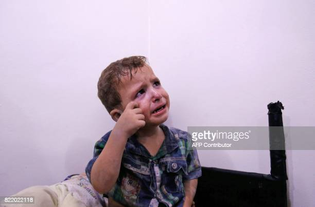 A Syrian boy cries as he waits to receive treatment at a makeshift hospital after he was injured in shelling on the rebelheld town of Arbin east of...