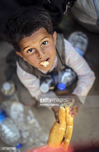 Syrian boy eats food after crossing into Turkey from Akcakale Border Gate in Sanliurfa Turkey on June 16 2015 Hundreds of Syrians fled from clashes...