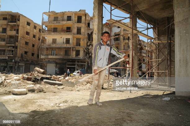 A Syrian boy helping with a building's reconstruction in the Syrian city of Aleppo Syria 24 June 2017 Large swathes of the city mostly in eastern...