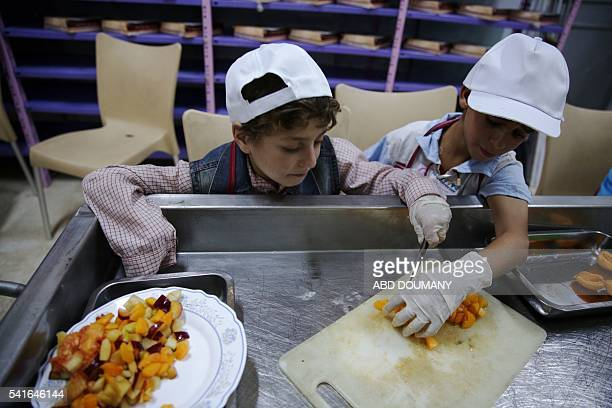 A Syrian boy helps an amputee cut fruits as they take part in a cooking competition to prepare iftar meals during the Muslim holy fasting month of...