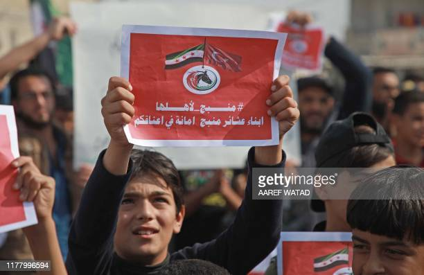 A Syrian boy holds a sign bearing an opposition flag and Turkey's national flag with a slogan that reads in Arabic Manbij is ours signed by he tribes...