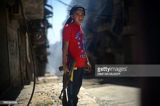 A Syrian boy holds an AK47 assault rifle in the majorityKurdish Sheikh Maqsud district of the northern Syrian city of Aleppo on April 14 2013 In...