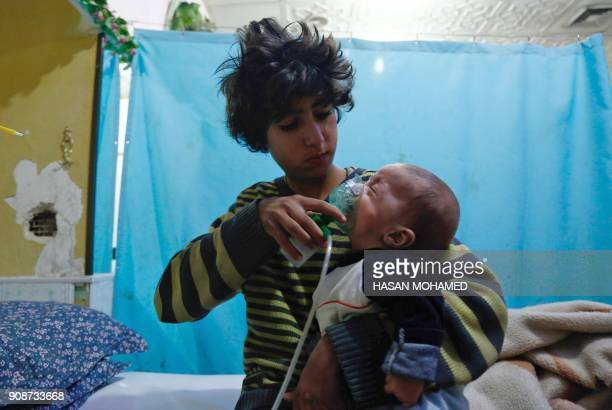 Syrian boy holds an oxygen mask over the face of an infant at a makeshift hospital following a reported gas attack on the rebelheld besieged town of...