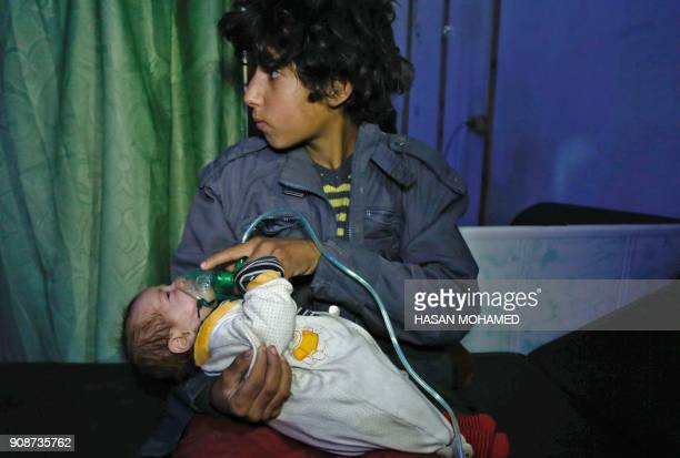 A Syrian boy holds an oxygen mask over the face of an infant at a makeshift hospital following a reported gas attack on the rebelheld besieged town...