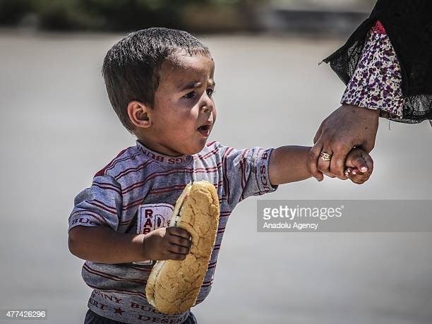 Syrian boy holds sandwich as he and his family return to the Syrian town of Tal Abyad from Turkey near Akcakale border crossing in Sanliurfa province...