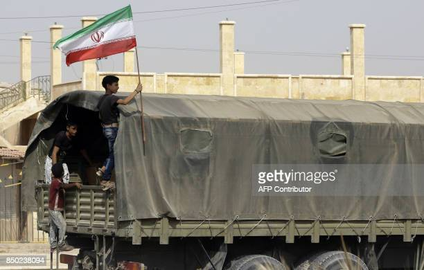Syrian boy holds the Iranian flag as a truck carrying aid provided by Iran arrives in the eastern city of Deir Ezzor on September 20, 2017 while...
