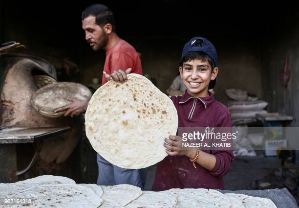 A Syrian boy holds up freshlybaked traditional bread in a bakery in the northern town of alBab on May 24 to be consumed during the Iftar fastbreaking...
