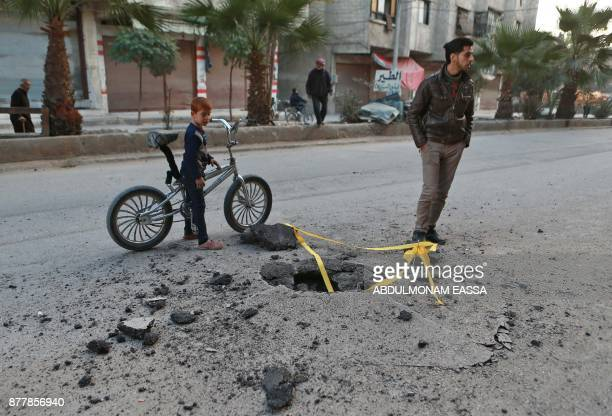 A Syrian boy looks at a hole in the ground caused by an undetonated rocket that fell following a reported air strike in the rebelcontrolled town of...