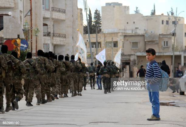 Syrian boy looks at rebel fighters from the Jaish alFatah brigades which include other rebel factions marching during a parade in the northwestern...