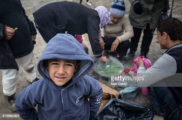 A Syrian boy looks at the camera as people cook outside at the Idomeni refugee camp on the Greek Macedonia border on March 16 2016 in Idomeni Greece...
